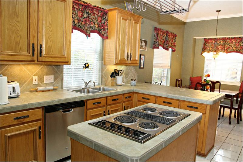 Spacious kitchen with plenty of storage opens to the breakfast bar and breakfast nook.