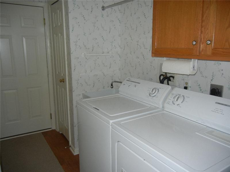 Laundry room with newer laminate flooring and washer and dryer included! right off the two car HEATED garage!