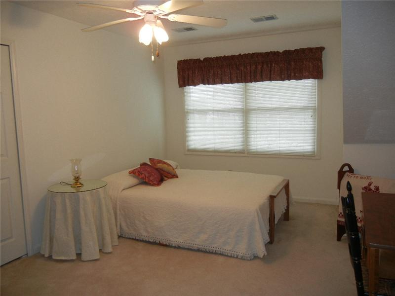 One of the large bedrooms on the second floor, freshly painted, neutral decor.