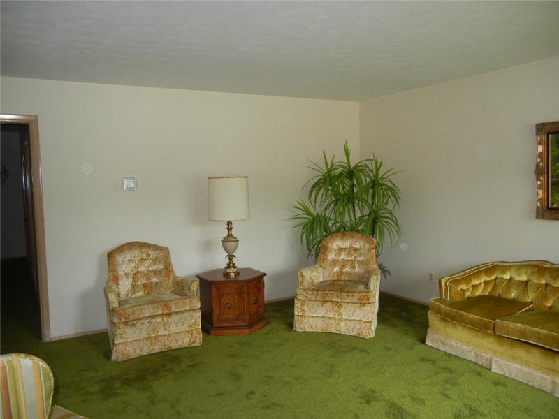 Spacious living room with neutral walls and hardwood floors underneath carpeting!